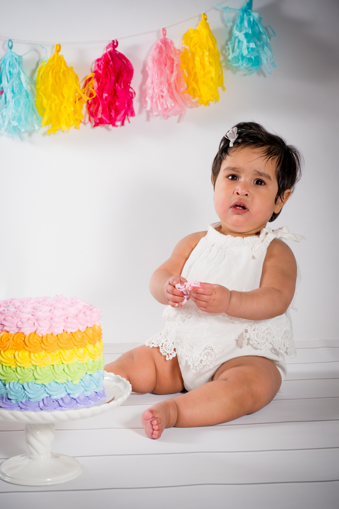 One year old girl next to her rainbow cake.