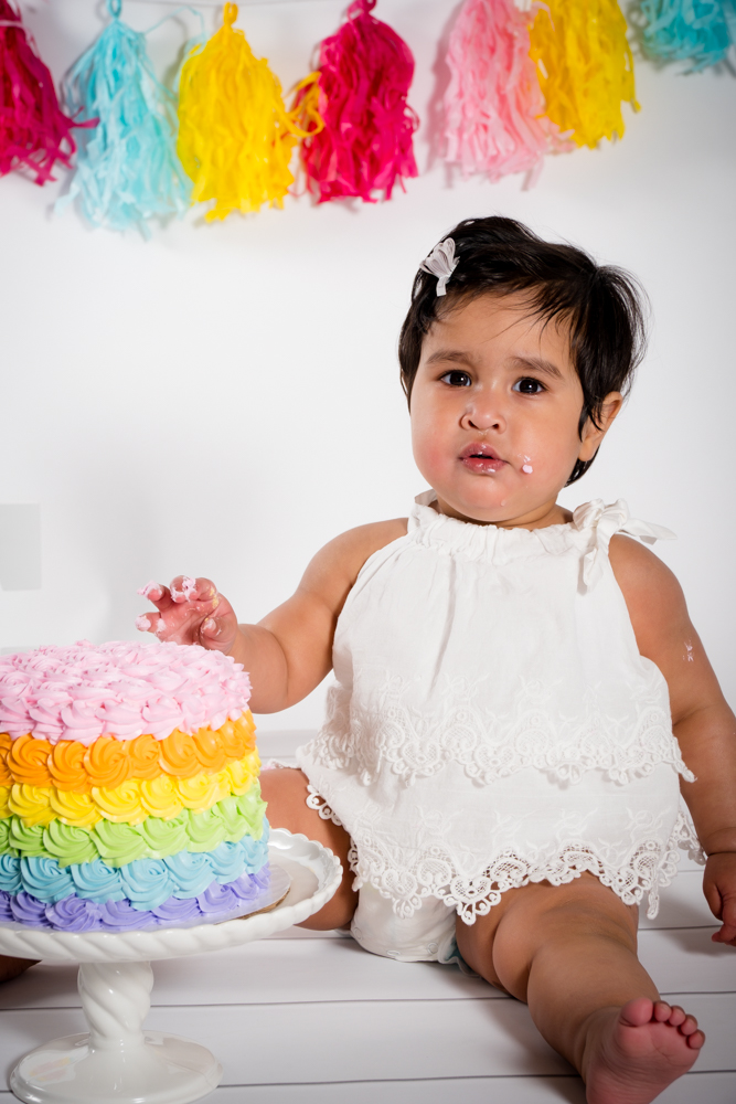 One year old girl next to her rainbow birthday cake with frosting on her hands and face