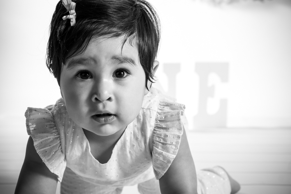 Adorable one year old girl crawling towards the camera in black and white.
