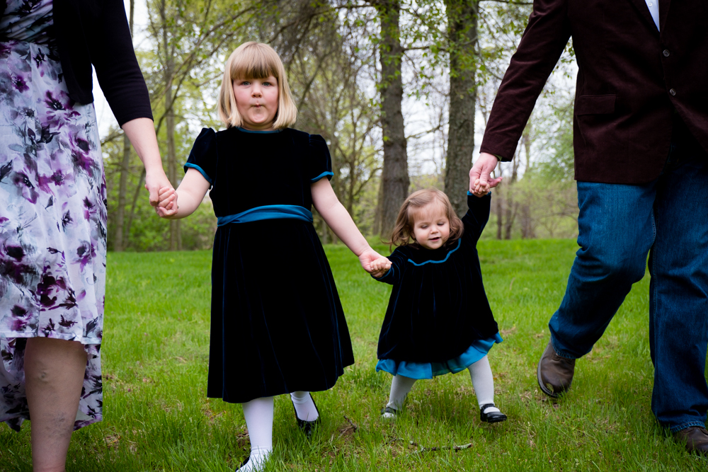 Two girls walking hold their parent's hands