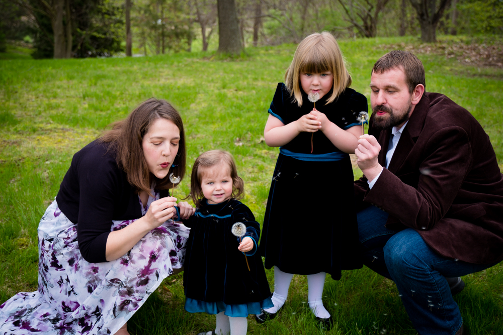 Two girls with their parents blowing dandelion seeds