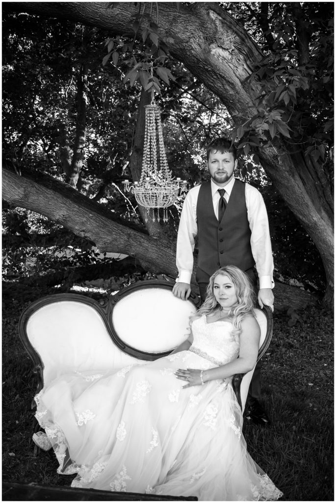 Black and white portrait of Hannah and Brandon in an outdoor space decorated by Rustic Heart Events.
