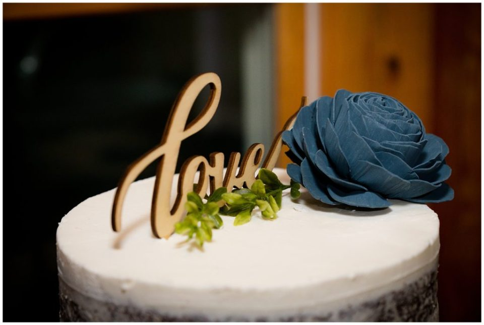 """The word """"love"""" carved out of wood as a cake topper for the wedding cake."""