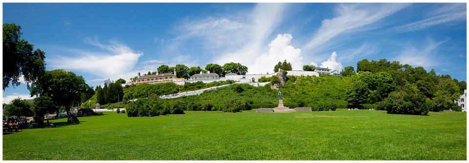 Fort Mackinac in panoramic with bright blue skies and green grass.