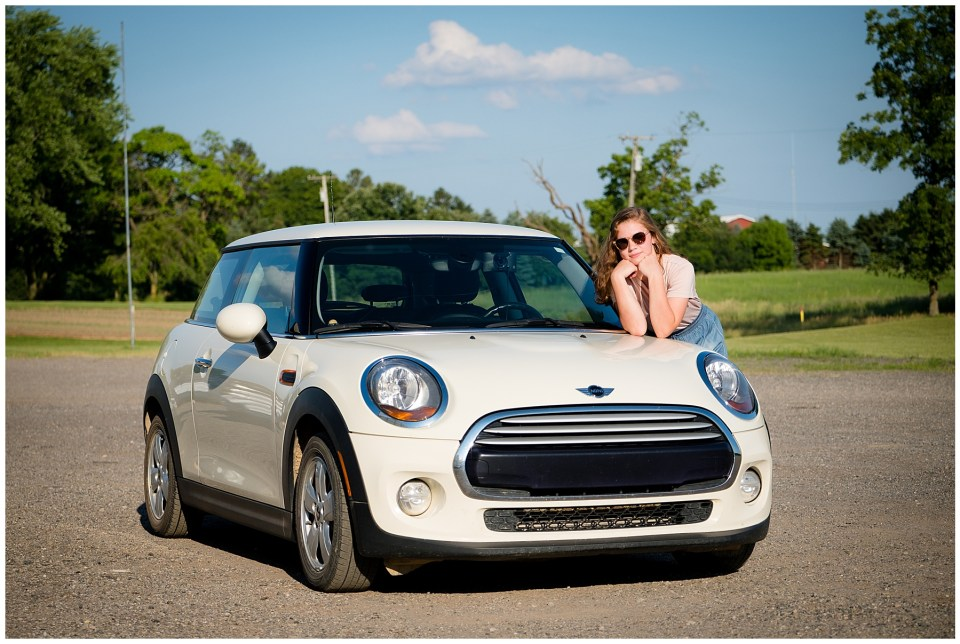 DHS senior girl with her mini coop car and wearing sunglasses.