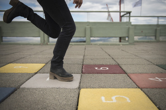 A game of hopscotch drawn on the pavement with numbers on the tiles