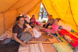 Two families in one of the tents in a yard of the church.