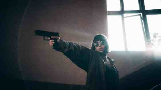 woman holding out a gun ready to shoot