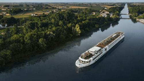 Uniworld's S.S. La Venezia River Cruise Ship down a river in Europe