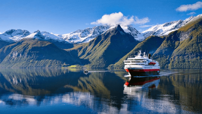 Hurtigruten ship on the Norwegian coast with mountains in the background