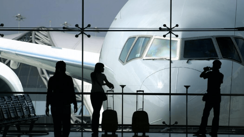 Silhouette of passengers standing by a plane near an airport window