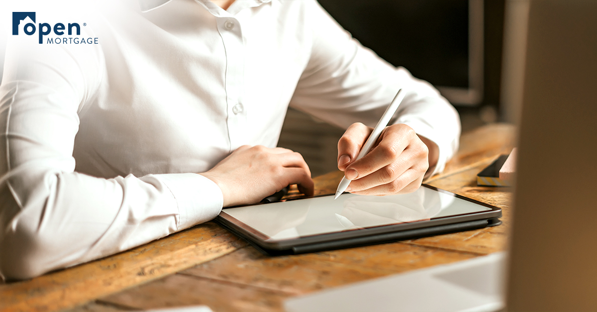man sitting at disk writing on digital tablet