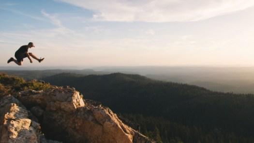 A man jumping on brown rock mountain during daytime