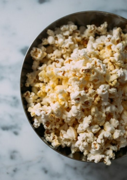 An image of a black bowl with popcorn in it placed at a white surface
