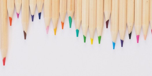 Image of coloured pencils place at the top of the white background