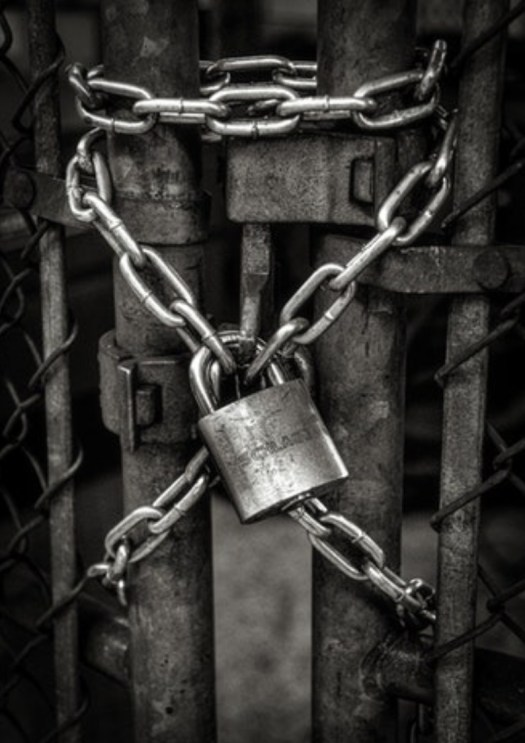 An image of a rusted pole where chains are wrapped arounf it with silver lock