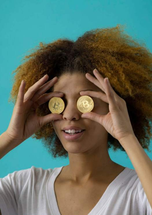 Image of a girl holding gold coins on her eyes