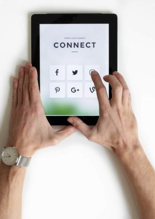 Image of a hands holding a tab in white bacjkground where the screen has social media signs
