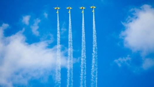 Four jets soaring high above in the sky billowing out white smoke