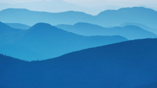 Photograph of range of mountains looking bluish in the late evening