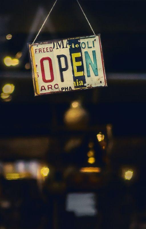 'Open' written on a board hanging outside a shop