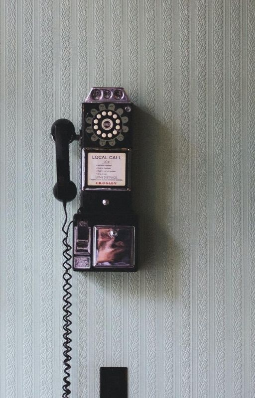 Vintage telephone hanging on grey wall