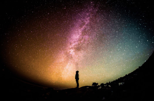A man standing at night time under an open sky full of stars