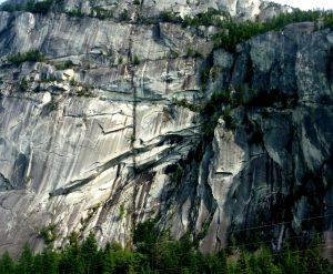Figura 3.21 El Jefe de Stawamus, parte del Complejo Costa Rango Plutonic, cerca de Squamish, BC El acantilado es de unos 600 m de altura. La mayoría de las rayas oscuras son el resultado de las algas y el crecimiento liquen donde la superficie es frecuentemente mojado, pero hay un gran (alrededor de 10 m de diámetro) dique vertical que se extiende desde abajo hacia arriba. [Foto SE]