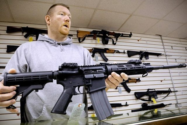 John Jackson, co-owner of Capitol City Arms Supply shows off an AR-15 assault rifle for sale Wednesday, Jan. 16, 2013 at his business in Springfield, Ill. President Barack Obama launched the most sweeping effort to curb U.S. gun violence in nearly two decades, announcing a $500 million package that sets up a fight with Congress over bans on military-style assault weapons and high-capacity ammunition magazines just a month after a shooting in Connecticut killed 20 school children. (AP Photo/Seth Perlman)