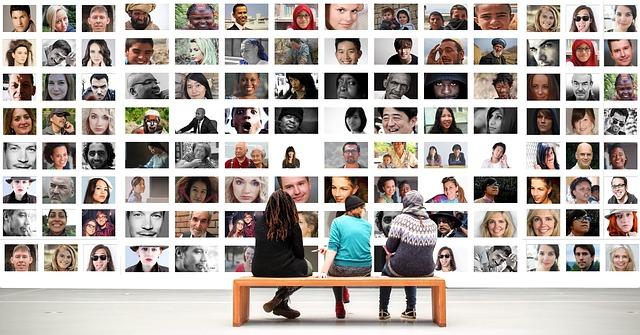 Trois personnes devant un mur de portraits.