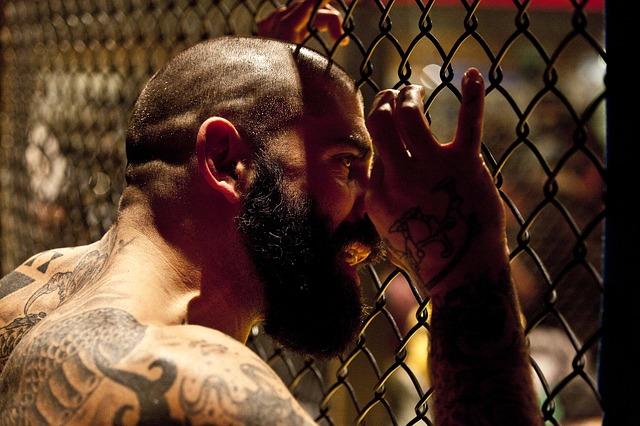 Homme barbu et tatoué aggripé à un grillage.