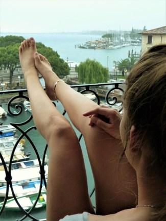 Jeune femme sur un balcon avec vue sur la mer.