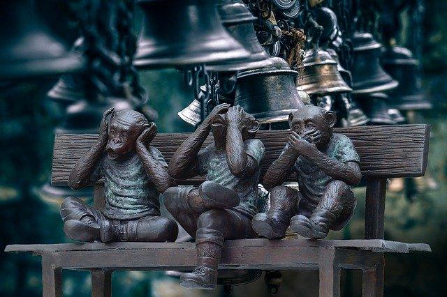 Figure des 3 singes (ne pas entendre, ne pas voir, ne pas parler) assis sous une rangée de cloches.