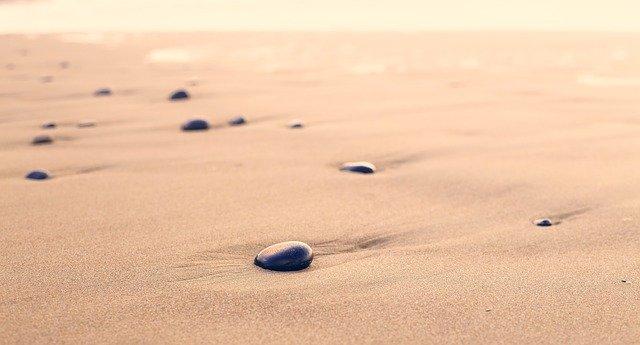 Galets disséminés sur une plage de sable fin.