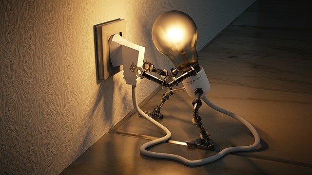 Photo d'un petit robot, donc la tête est constituée d'une ampoule, en train de brancher lui même son alimentation dans une prise murale.  Métaphore de la créativité et des idées.
