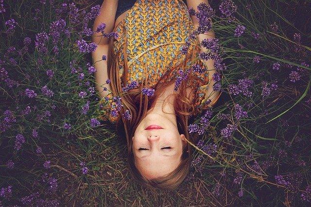 Photo d'une jeune femme, allongée dans un champ de fleurs mauves, les yeux fermés et un sourire aux lèvres.
