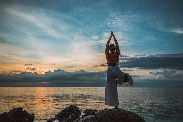 Photo plus colorée d'une femme dans la même posture, sur un rocher devant la mer, soleil levant aussi.