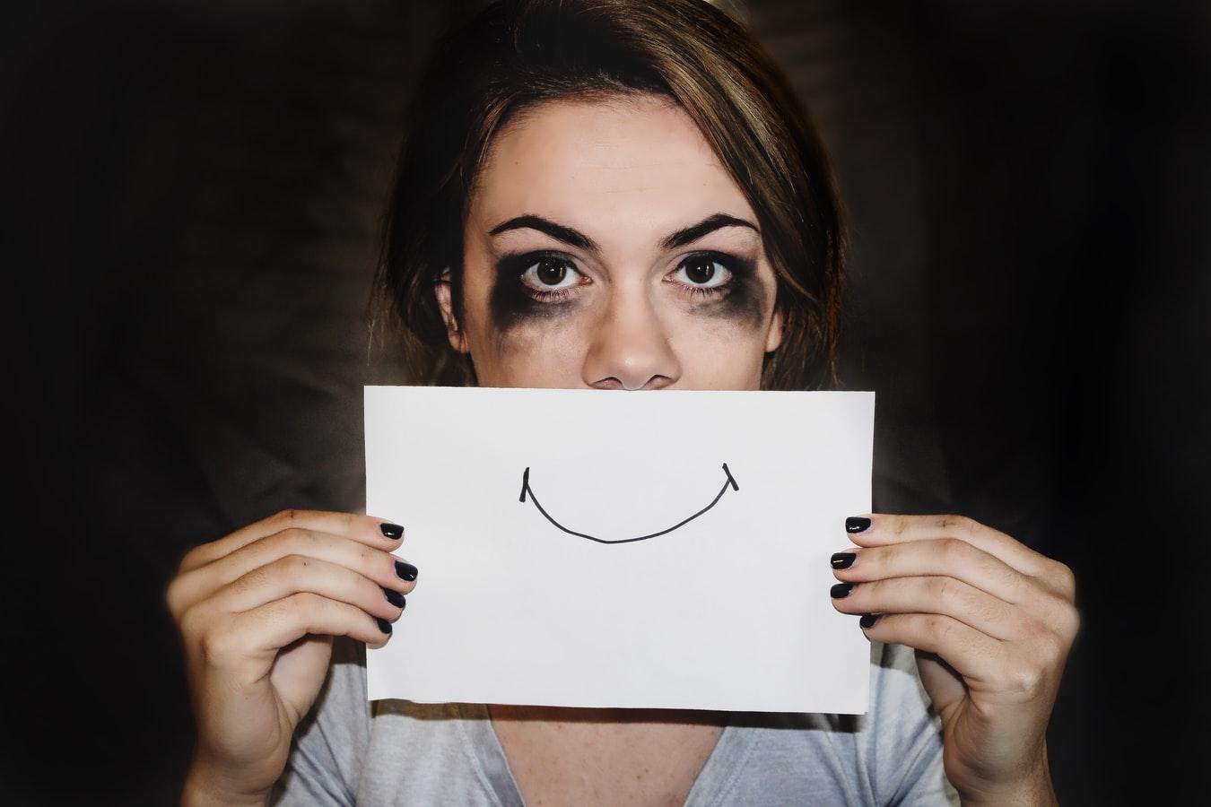 Une femme battue tenant une feuille representant un sourire contraint.