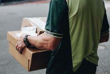 Un homme livrant des produits emballés dans des cartons.