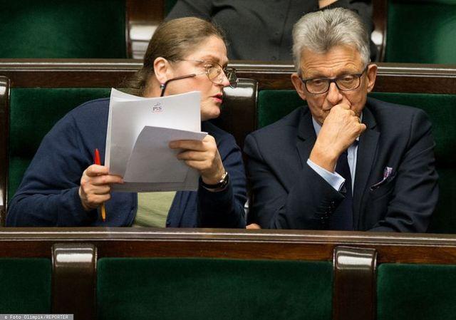 Krystyna Pawłowicz iStanisław Piotrowicz siedzą oboksiebie wławach sejmowych.  Ona, trzymając kartki idługopis, patrzy naPiotrowicza. On, pojej lewej stronie, siedzi zamyślony.