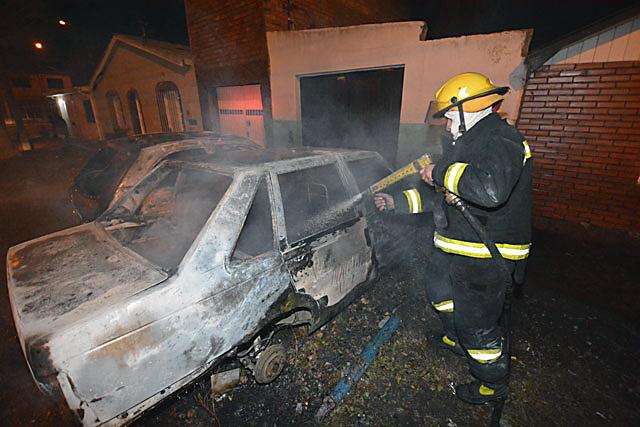 Un bombero extingue las llamas de un vehículo incendiado - Foto: La Opinión Austral