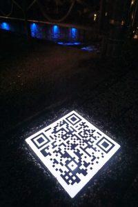 Stadtspaziergang mit beleuchteten QR-Codes im Bürgersteig