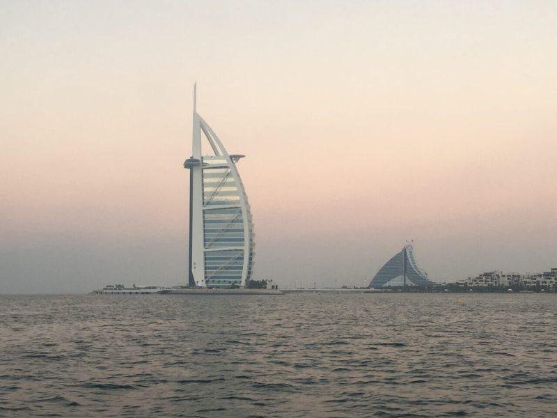 Das Hotel Burj Al Arab in Dubai bei Sonnenuntergang vom Wasser aus gesehen.