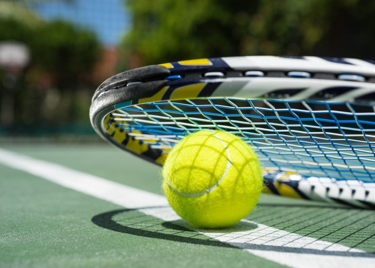 Close up view of tennis racket and balls on tennis court