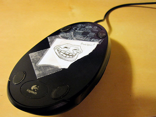 Tape a drawing of the troll face to the bottom of your coworker's mouse.