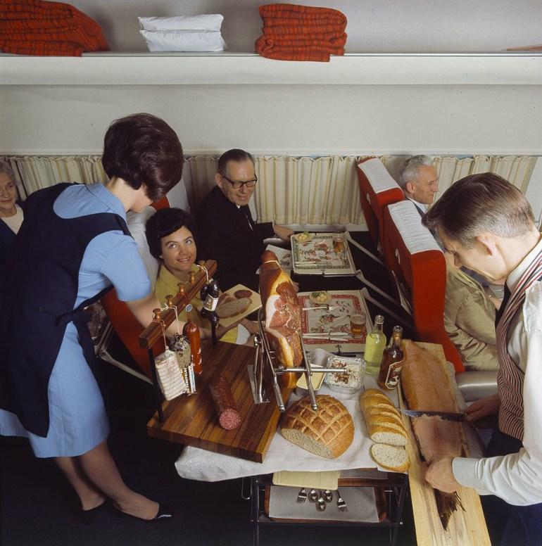 A flight attendant serving Scandinavian Country Style Buffet on Scandinavian Airlines in 1969.