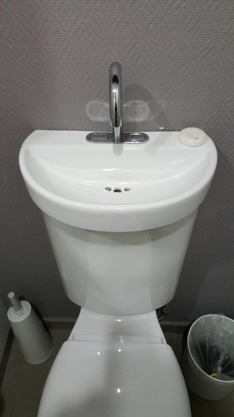 A sink built into the top of a toilet.