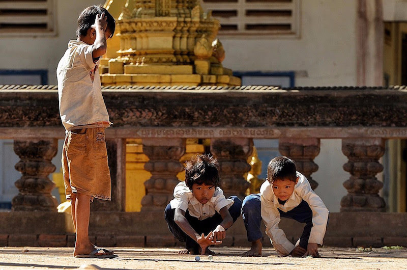 """Boys playing marbles in Cambodia"" Cambodia"