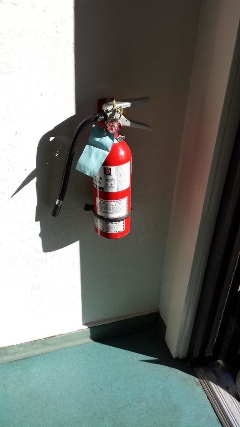 This fire extinguisher's shadow looks like a grouchy man's face.