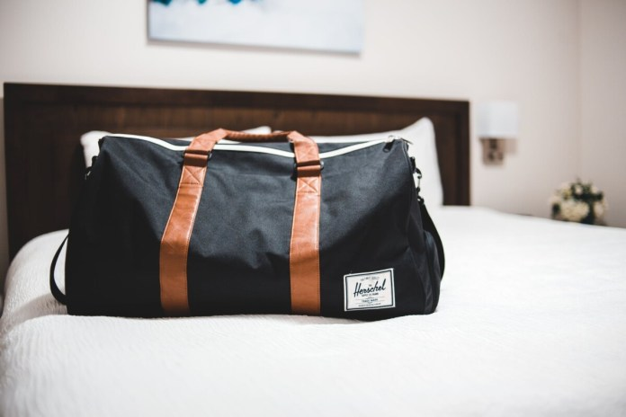 modern sports bag on bed in hotel room